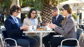 Businesspeople drinking coffee and talking in the outdoor cafe, steadycam shot