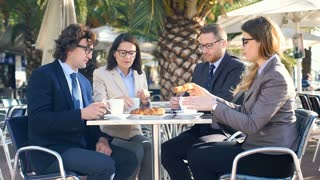 Businesspeople eating croissants and drinking coffee in the outdoor cafe, steady