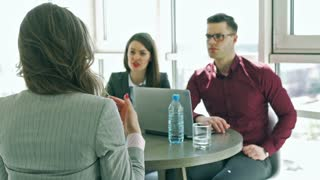 Businesspeople interviewing a woman in the office