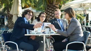 Businesspeople looking on smartphone and sitting in the outdoor cafe, steadycam