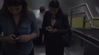 Businesspeople riding on escalator, slow motion shot at 240fps, steadycam shot