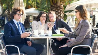 Businesspeople sitting in the outdoor cafe and using electronics, steadycam shot