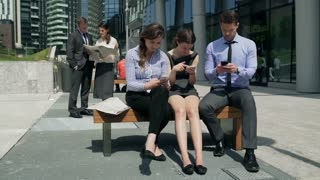 Businesspeople sitting on the bench and using smartphones, steadycam shot