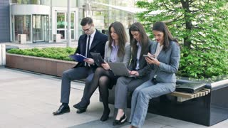 Businesspeople sitting on the bench and working on modern technology