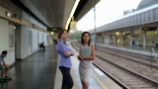 Businesspeople standing on the train station with coffee cup