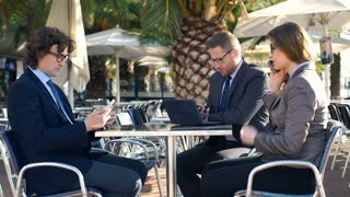 Businesspeople talking on cellphone and sitting in the outdoor cafe, steadycam s