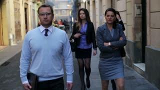 Businesspeople walking on street, steadycam shot.