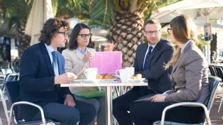 Businesspeople working on documents in the outdoor cafe, steadycam shot