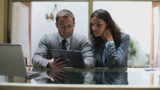 Businesspeople working together on tablet in the office, steadycam shot