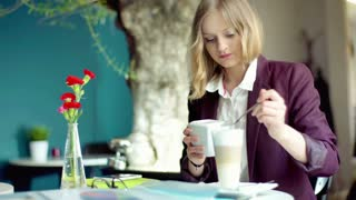 Businesswoman adding sugar to the coffee and relaxing