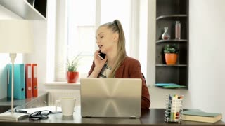 Businesswoman answers cellphone and standing next to the window while talking, s