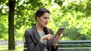 Businesswoman browsing internet on smartphone in the park