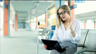 Businesswoman chatting on laptop with someone while sitting on platform