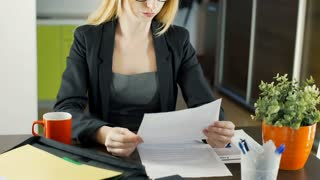 Businesswoman checking documents and smiling to the camera, steadycam shot