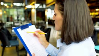 Businesswoman circle something on the papers in the cafe
