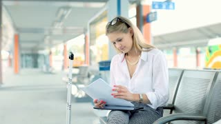 Businesswoman compares data from papers and tablet while sitting on platform
