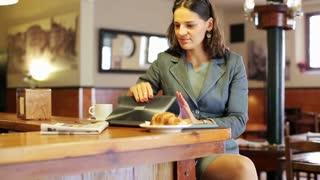 Businesswoman finish working on laptop start reading newspaper, steadycam shot.