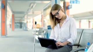 Businesswoman finish working on laptop while sitting on platform