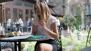 Businesswoman finishes working and eating lunch in the outdoor cafe