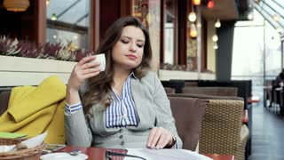 Businesswoman holding coffee and reading papers in the outdoor cafe