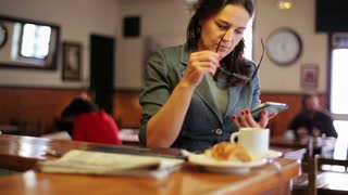 Businesswoman in glasses using cellphone in cafe, steadycam shot.