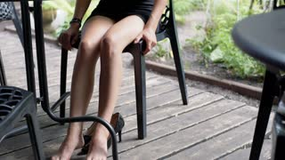 Businesswoman moves her tired feet and working in the outdoor cafe, steadycam sh
