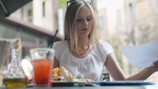 Businesswoman reading documents and eating lunch in the outdoor cafe