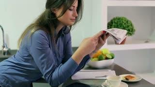 Businesswoman reading newspaper in the kitchen
