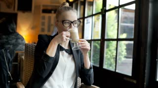 Businesswoman relaxing in the cafe and drinking coffee, steadycam shot