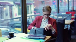 Businesswoman sitting in the cafe and taking pen from the bag