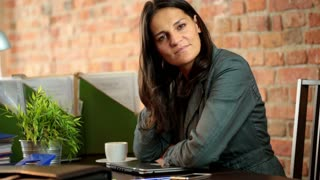 businesswoman sitting in the office and smiling to the camera