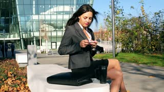 Businesswoman sitting outside with smartphone and smiling to the camera