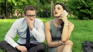 Businesswoman talking on cellphone and businessman waiting for her
