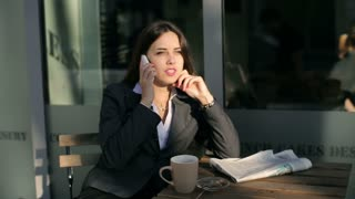 Businesswoman talking on cellphone outside the cafe and relaxing