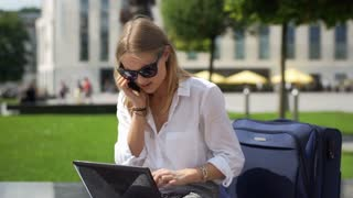 Businesswoman talking on cellphone while working on laptop outdoors