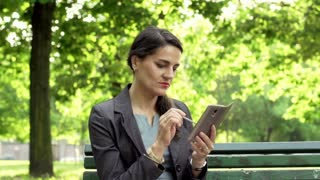 Businesswoman using smartphone in the park