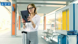 Businesswoman using tablet and smiling to the camera on platform
