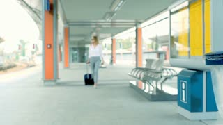 Businesswoman walking with suitcase and checking time on watch, steadycam shot