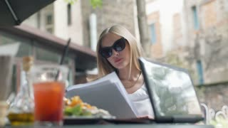 Businesswoman wearing sunglasses and reading documents in the outdoor cafe