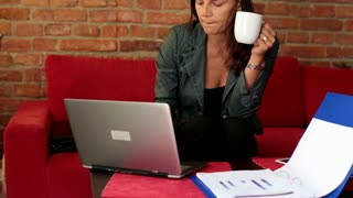 businesswoman with a cup of coffee working on her laptop and looking to the documents