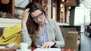 Businesswoman working on documents and having headache in the cafe