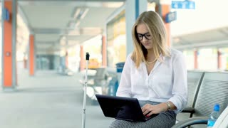Businesswoman working on laptop while sitting on the train station