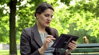 Businesswoman working on tablet and smiling to the camera in the park