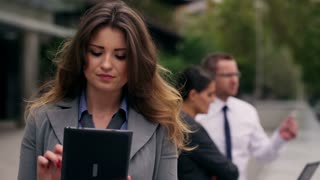 Businesswoman working on tablet on public square, steadycam shot