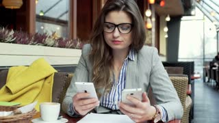 Businesswoman working on two smartphones and doing serious look to the camera