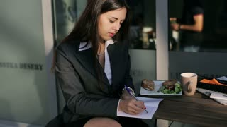 Businesswoman writing notes in the cafe and smiling to the camera