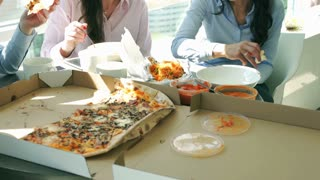 Businesswomen eating pizza in the office on the break