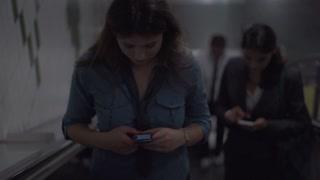 Businesswomen riding on escalator, slow motion shot, steadycam shot