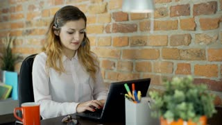 Call center agent looks busy while talking with client and working on laptop