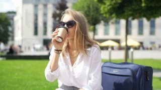Calm businesswoman drinking coffee and checking time while sitting outdoors